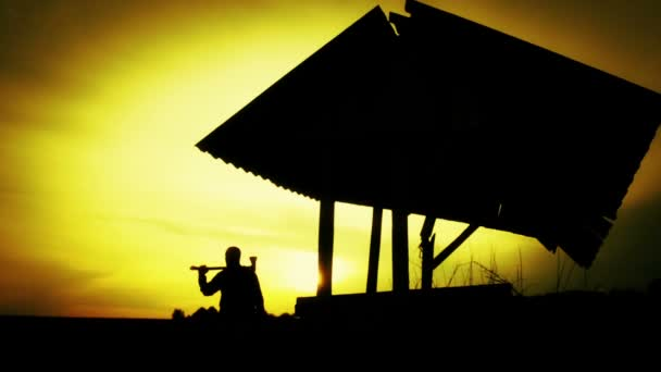 Silhouette of a man at sunset in the field. Silhouette of a man with an ax in the old well. Silhouette at sunset Lumberjack, woodcutter. Man, nature, sunset.
