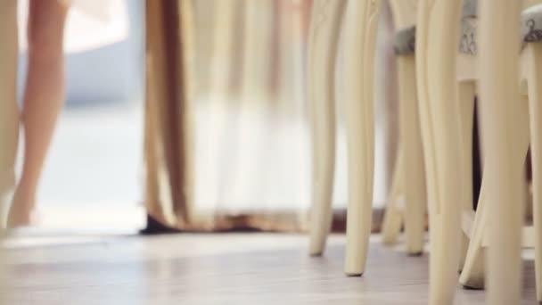 Beautiful female legs in walking. Feet girl model sitting in a cafe. Female feet in shoes. Very beautiful female gait.