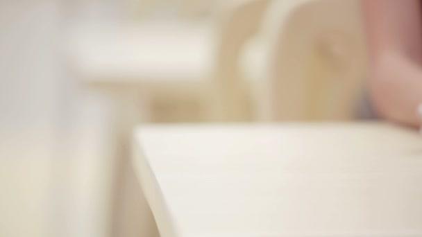 Ruka se zamasková s kyticí levandulovou. Ruce mužů a žen se s kyticí květinám uctí. Manova ruka klade na stůl kytici levandule.