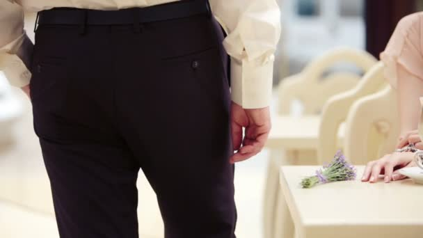 A man walks past the table at a restaurant. Rear view of a man walking on the way out of the cafe.