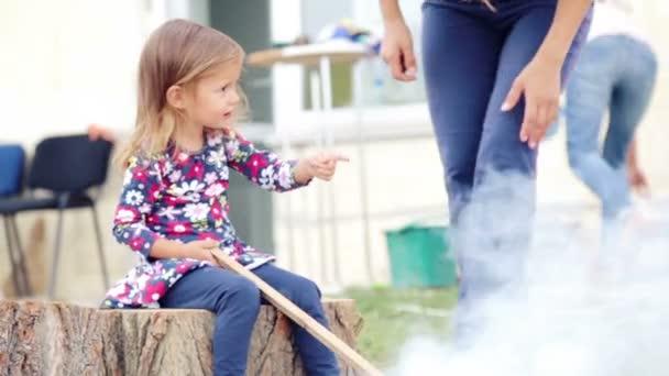 Malá holka sedí doma u grilu. Kavkazská holčička u ohně v blízkosti domu