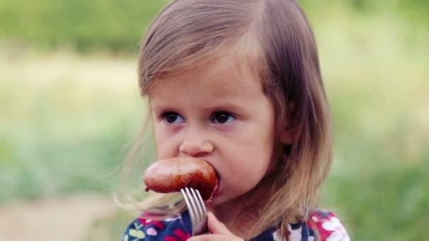 Kavkazská holčička jí grilovací klobása. Dítě jí dívku v přírodě. Emotsonalny dítě jí zdravé jídlo chutná. Portrét dítěte na jídlo