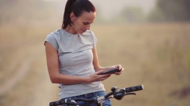 Krásná mladá dívka na přírodu s smartphone. Portrét dívky na kole s telefonem