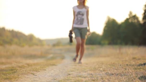 Krásná mladá žena novinář v stepi. Dívka s kamerou na přírodu. Mladá žena s kamerou na safari. Cestování, turistika, dobrodružství.