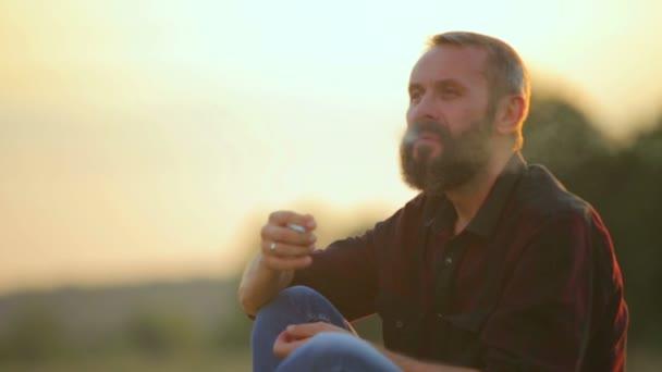 Portréja egy szakállas férfi, a cigarettát. Érzelmi ember: a fényképezőgép dohányzik