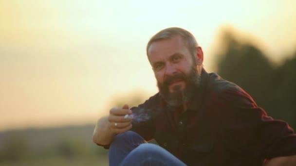 Porträt eines bärtigen Mannes mit Zigarette. Emotionaler Mann raucht vor der Kamera.