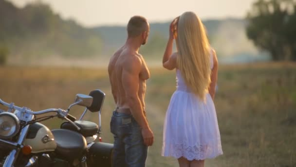 Man and woman on a motorcycle outdoors. In love with a young beautiful couple on a motorcycle in the country.