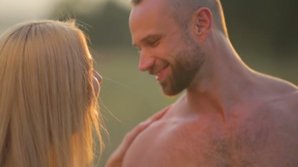 A young man and woman in the park at sunset. Happy young couple enjoying an intimate moment on the nature. Portrait of a young couple embracing and kissing.