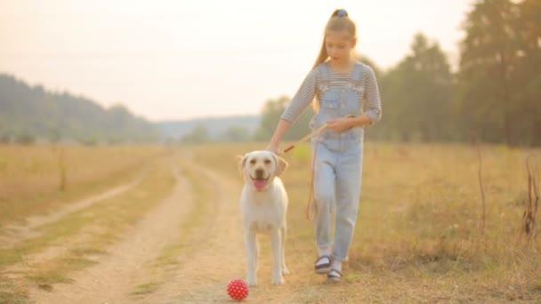 ein Kind mit seinem Hund im Freien. Porträt des Mädchens mit ihrem Hund vor dem Haus. Mädchen geht mit Hund spazieren.