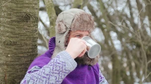 Vousatý muž pití čaje v lese. Vousatý dřevorubce v klidu v zimě.