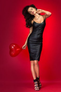 Lovely brunette woman with heart balloon.