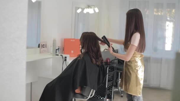 Hairdresser makes the final stage of creating a hairstyle for a cute girl, rear view. Professional hairdresser stylist makes a hairstyle for a cute European little girl in the house.