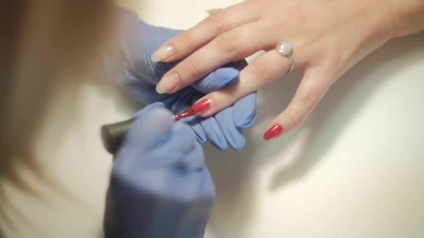 Hardware-Maniküre. Schöne Frauenhände. Fingernagelbehandlung, Herstellung Prozess. Elektrischer professioneller Nagelfeilenbohrer in Aktion. Schönheits- und Handpflegekonzept