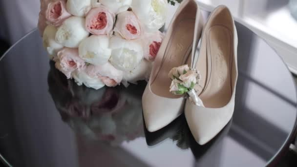 Wedding bouquet of white fresh peonies.wedding jewelry lies next to womens shoes shrouded in a veil. shoes are reflected in the glass. there is a place to insert text