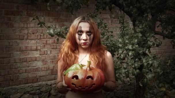 Mladá sexy žena čarodějnice drží vyřezávané dýně, Halloween pozadí
