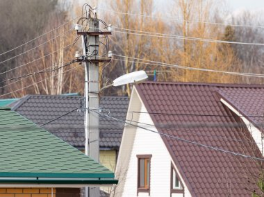 Bearing electric wires on a background of roofs