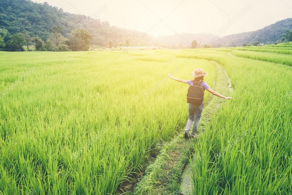 Woman traveler walking on green rice terraces field