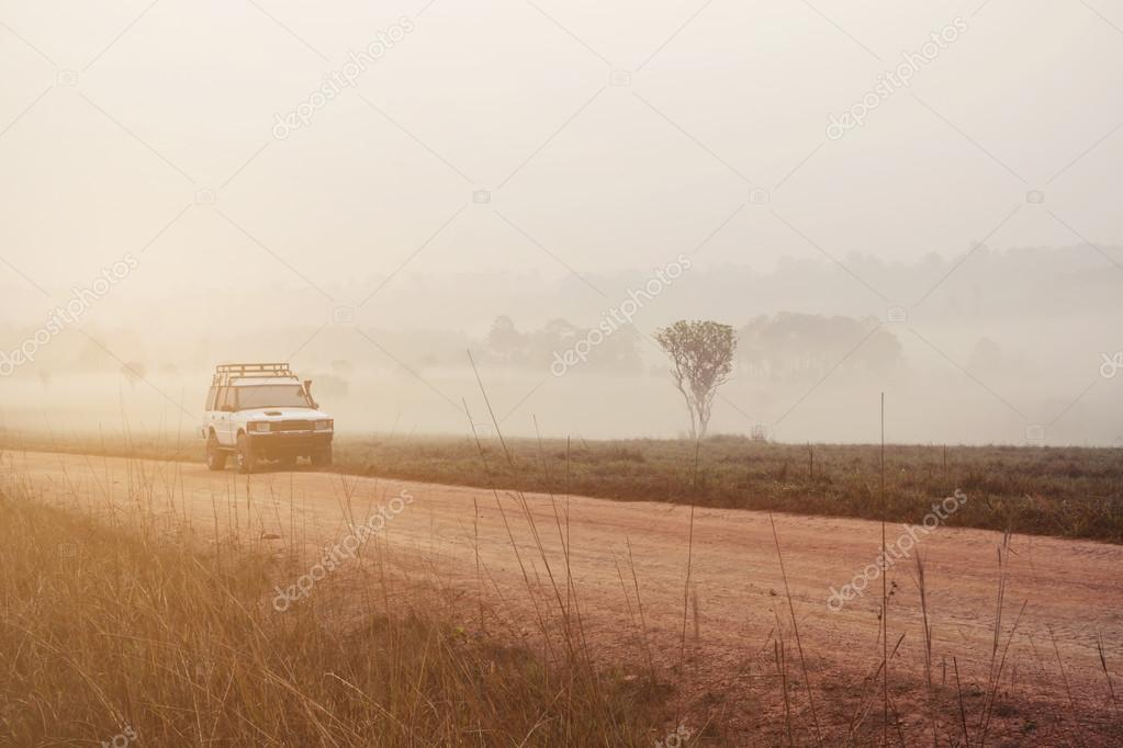 car on the road in the valley with sunrise and mist