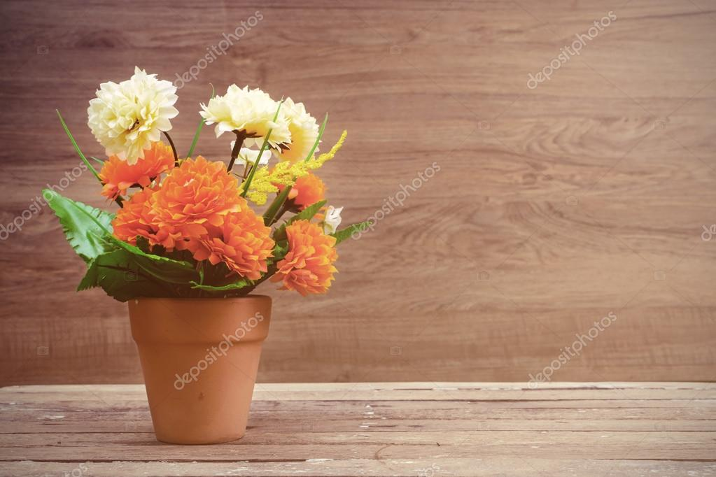Flowers and pot on old wooden table