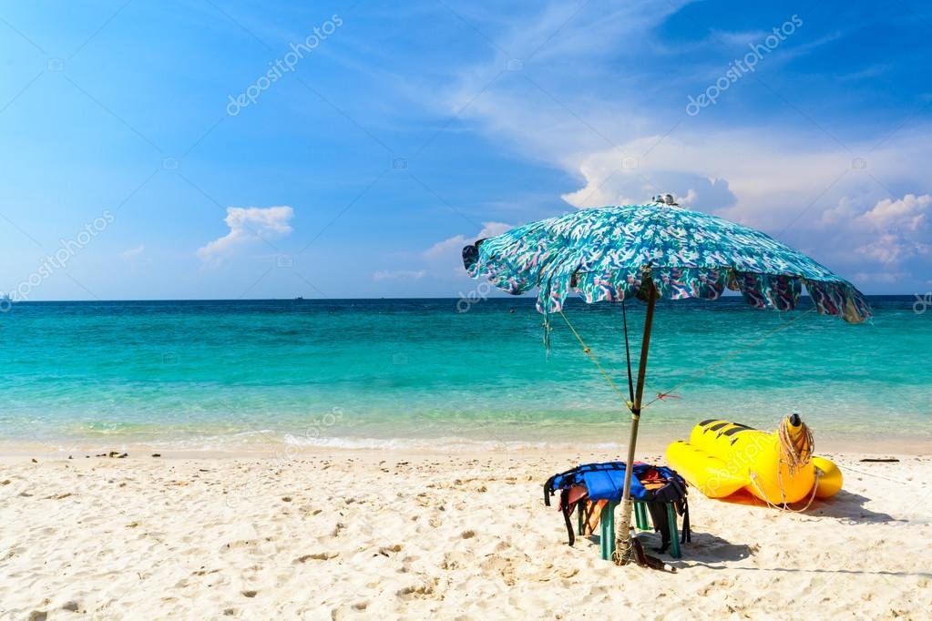 Umbrella and banana boat at beach with blue sky in summer