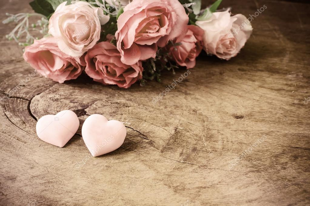 Heart shape with pink rose flower on wooden table