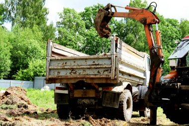 An excavator loads earth into an old truck. Excovator bucket