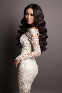 sensual asian woman with long dark hair in elegant lace dress