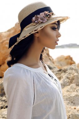 beautiful girl with dark hair wears casual elegant clothes and hat