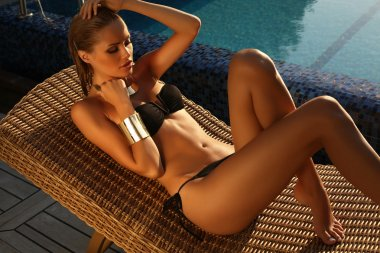 sexy girl with blond hair in bikini relaxing beside a swimming pool