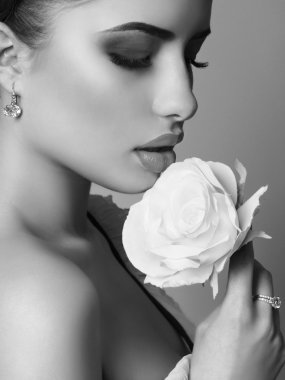portrait of beautiful woman holding white rose