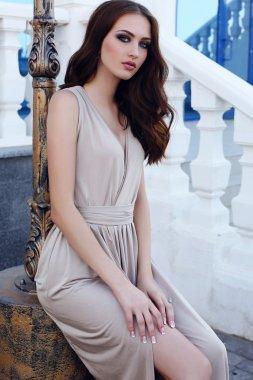 beautiful girl with dark hair and blue eyes in elegant beige dress