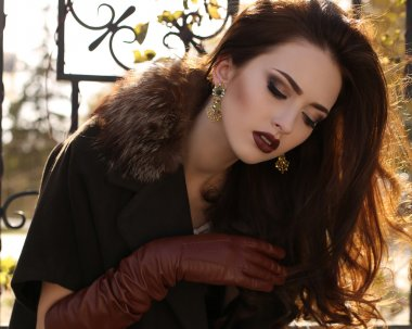 portrait of elegant lady wearing coat and leather gloves