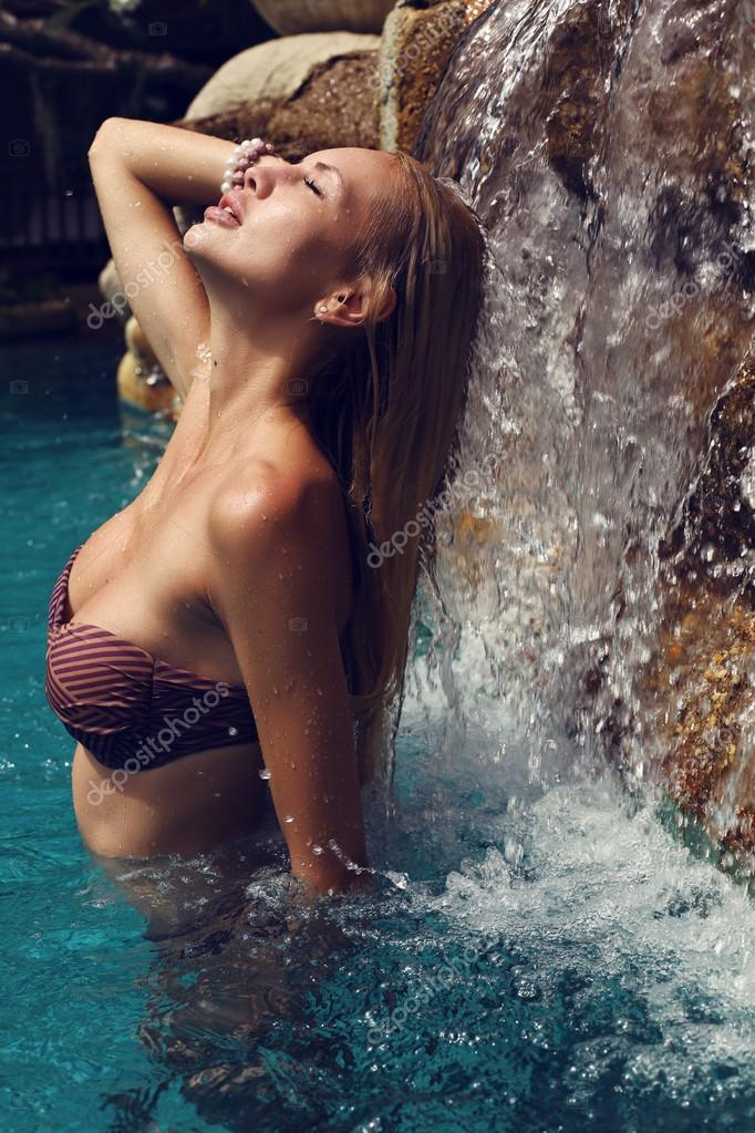 sexy woman in bikini relaxing under waterfall in Thailand