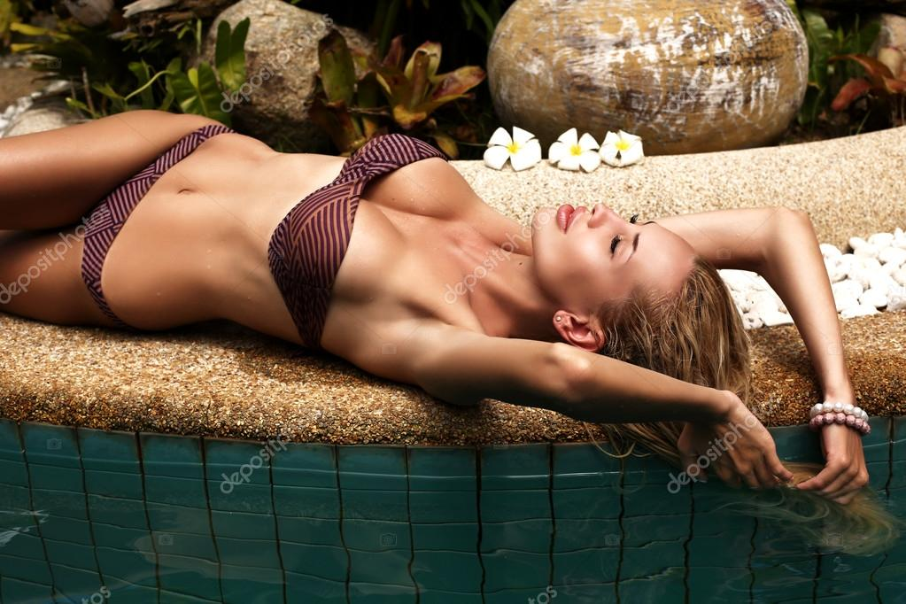 sexy woman with blond hair in bikini relaxing in swimming pool
