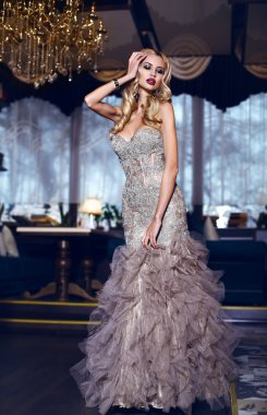 gorgeous woman with blond hair in elegant dress posing in luxury interior