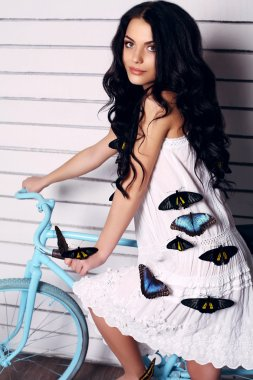 pretty brunette woman posing with a lot of colorful butterflies