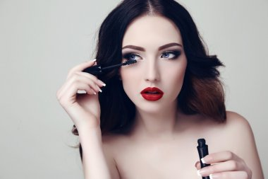 sexy woman with dark hair and bright makeup with mascara