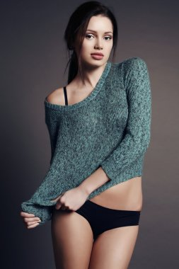 woman with dark hair and natural makeup in cozy cardigan