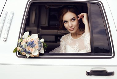 sensual bride with dark hair in luxurious wedding dress posing in car