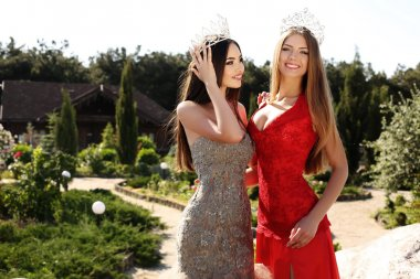 beautiful girls wearing elegant dresses and luxurious crown