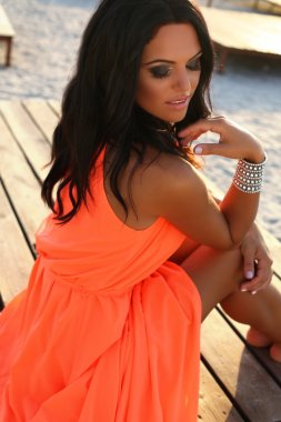 sexy girl with dark hair in elegant dress relaxing on beach