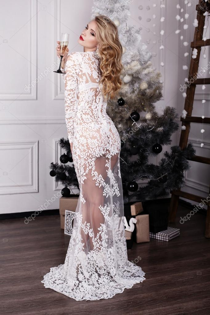 Girl with blond hair wears luxurious dress,posing beside Christmas tree