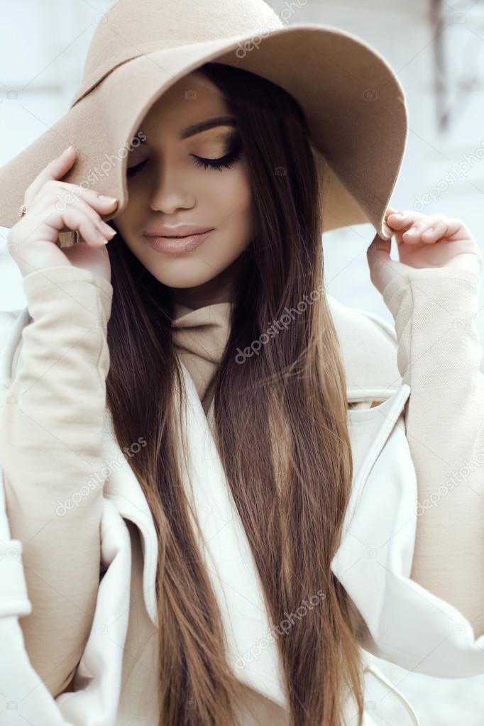 320cc40ed1 Muchacha de glamour con el pelo lacio oscuro luce lujoso abrigo beige con elegante  sombrero —