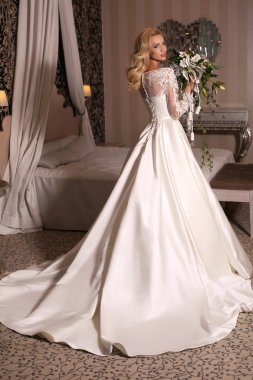 gorgeous woman with blond hair wears luxurious wedding dress with bouquet