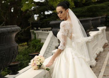 gorgeous bride with dark hair wears elegant wedding dress