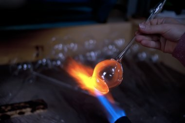 Melting glass piece in flame