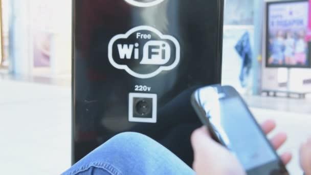 Dívka s mobile v oblasti bezplatné Wi-Fi