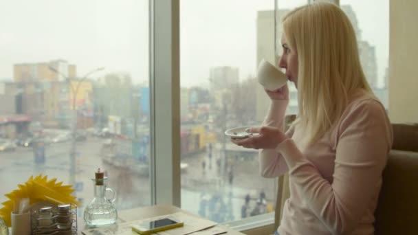 Dívka, pít čaj v kavárně a při pohledu z okna