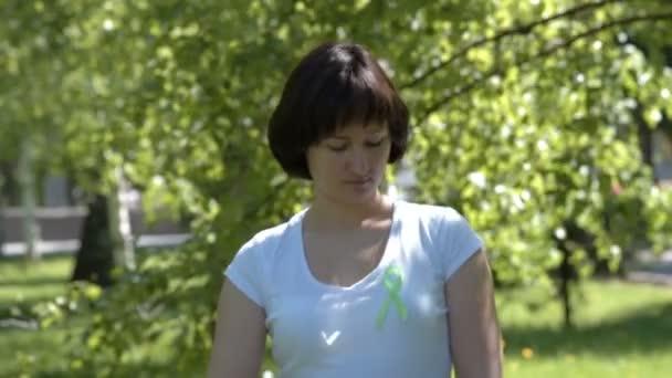 Woman pinning lime green awareness ribbon