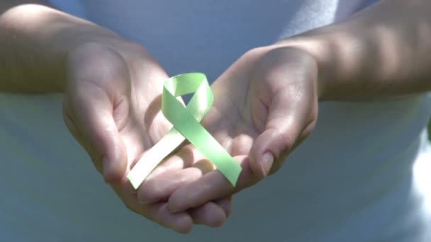 Woman holding lime green awareness ribbon in hands